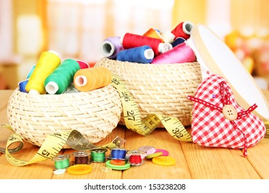 Wicker baskets with accessories for needlework on wooden table, on bright background