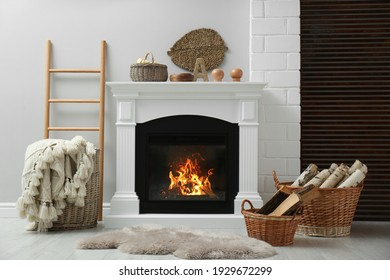 Wicker baskets with firewood and white fireplace in cozy living room