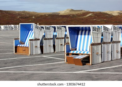 Wicker beach chairs on a parking lot on the island of Sylt, Germany, before the beginning of the bathing season