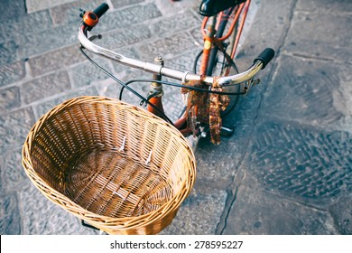 Wicker bicycle basket. Vintage bike on the street as background. Top view to the cobblestone