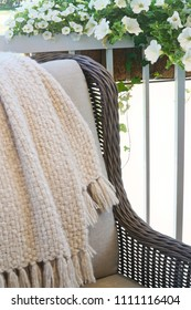 Wicker chair with blanket and flowers