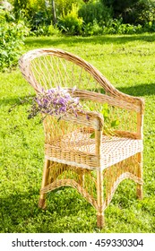 Wicker chair with flowers on green field.