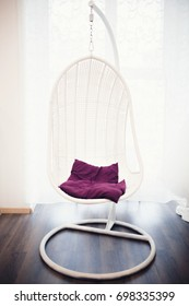 wicker chair chair hangs on chains in a white cafe room, a restaurant, a shop with walls, a red purple pillow.