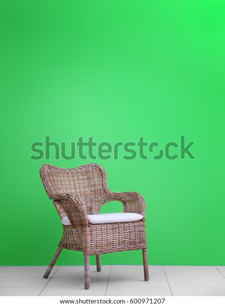 Wicker chair on green wall background