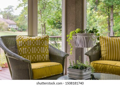 Wicker chairs with bright yellow cushions are a cheerful addition to the screened in porch.