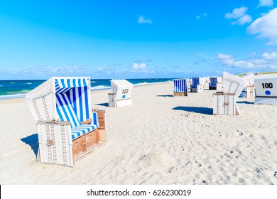 Wicker chairs on sandy beach in Kampen village on Sylt island, North Sea, Germany