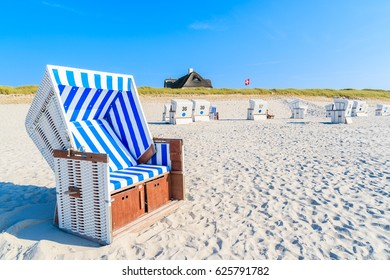 Wicker chairs on white sand Kampen beach with typical Frisian house roof in background, Sylt island, North Sea, Germany
