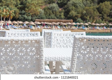 Wicker chairs in the restaurant on the beach. A view of the sea and a symbol of enjoying solitude.