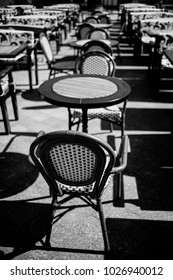 Wicker chairs and tables, cafes. Outdoor traditional cafe with old wood tables and wicker chairs. Wicker table and chairs in empty cafe on the street in the city. black and white photo