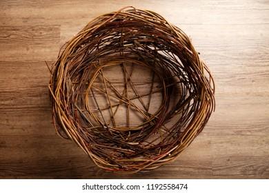 Wicker circular basket, in red and brown tones, against an oak floor.