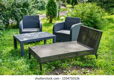 Wicker comfortable furniture made of plastic on grass in garden outside the city