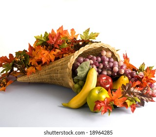A wicker cornucopia filled with fruits and autumn leaves