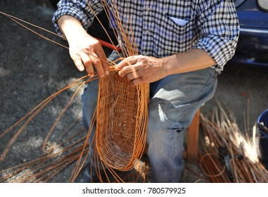 Wicker craftsman working outdoors manufacturing a basket, Spain