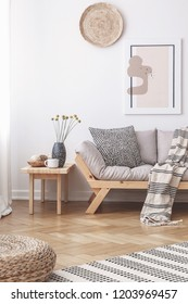 Wicker decorations and a painting on a white wall above a wooden sofa with cushions in a bright living room interior