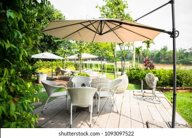 Wicker furniture, outdoor chair set and white umbrella in the garden