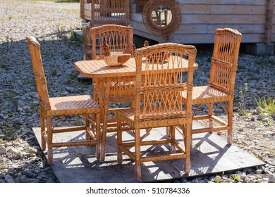 Wicker furniture set - table and four chairs, on the table there are two braided sweets bowls in the form of cocks