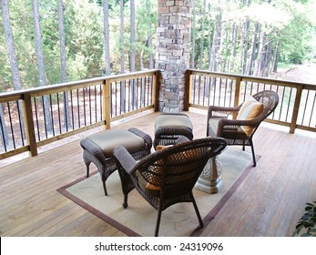 Wicker furniture sitting on a wooden deck overlooking a pine tree forest