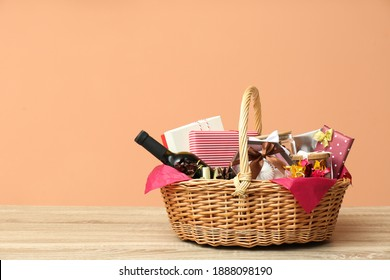 Wicker gift basket with bottle of wine on wooden table. Space for text - Shutterstock ID 1888098190