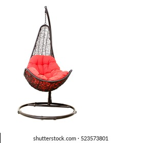 Wicker hanging chair swing hanging on a chain with red pillow isolated on white background