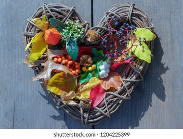 Wicker heart filled with autumn leaves and berries of firethorn, Virginia creeper, peel of beech nuts, flowers of snowball and lampion plant.