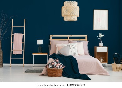 Wicker lamp hanging above double bed in real photo of bedroom interior with dark blue wall, flowers on bedside table and ladder with blanket