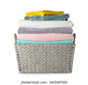 Wicker laundry basket with clean towels on white background