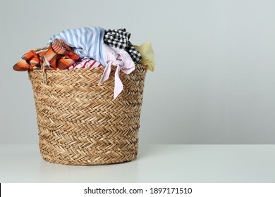 Wicker laundry basket with different clothes on light background. Space for text