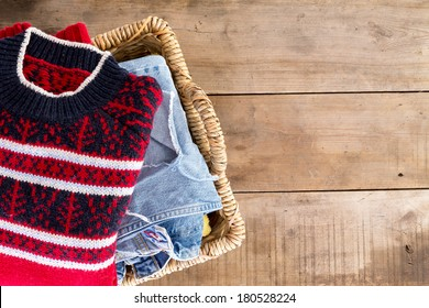 Wicker laundry basket filled with clean fresh washed winter clothes viewed from overhead standing at an angle on rustic wooden boards with copy space on the right