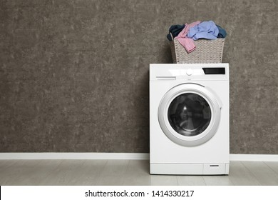 Wicker laundry basket full of dirty clothes on washing machine near color wall. Space for text
