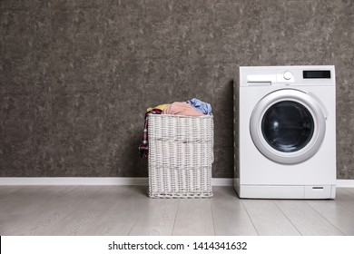 Wicker laundry basket full of dirty clothes and washing machine near color wall. Space for text