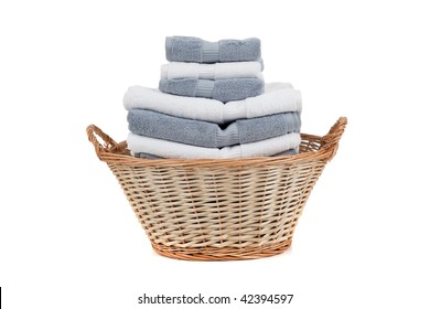 A wicker laundry basket full of white and gray towels on a white background