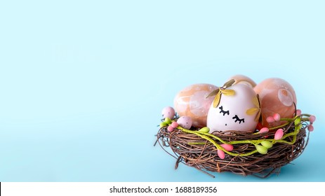Wicker nest, basket with pink golden decorated eggs isolated on blue background. Ester banner greeting card, promotion flyer. Copy space, front view, vibrant colours