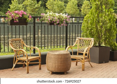 wicker outdoor furniture - two chairs and a round table - stand on the pedestrian promenade of a small river on a sunny day