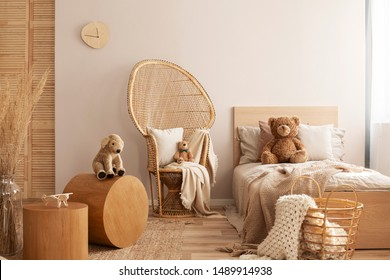Wicker peacock chair with pillow, armchair and toy in beige and wooden baby bedroom interior