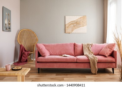Wicker peacock chair with red blanket behind pink velvet couch