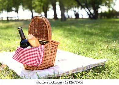 Wicker picnic basket with bottle of wine and bread on blanket in park. Space for text