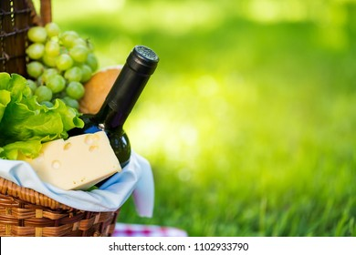 Wicker picnic basket with cheese and wine on red checkered table cloth on green grass outside in summer park, no people