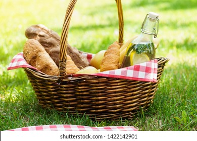 Wicker picnic basket with food and drink in a park. Summer picnic on the grass or lawn.