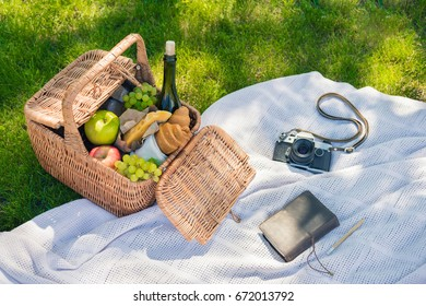 Wicker picnic basket with fruits and wine, vintage camera and notebook with pencil on green meadow