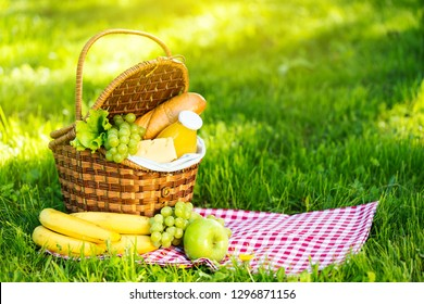 Wicker picnic basket with healthy food on red checkered table cloth on green grass outside in summer park, no people