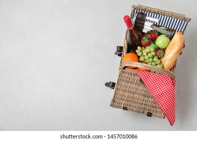 Wicker picnic basket with wine and different products on white background, top view