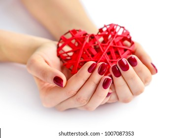 Wicker red heart in woman's hands on white background. Closeup heart in hand of girl with red manicure. Happy Valentines day, love concept.
