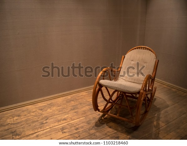 Wicker rocking chair in empty room with wooden floor, concept indoor composition