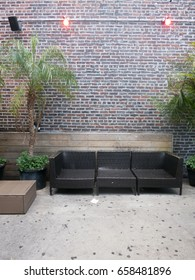 Wicker seating against an exposed brick wall on rooftop bar in New York City. Outdoor furniture on Manhattan rooftop bar in the summer, black chairs and palm trees in planters.