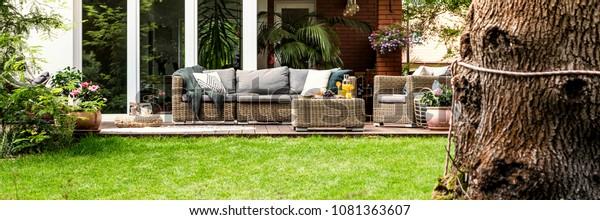 Rieten bank met kussens en tafel met fruit en sap staan op terras in de tuin bij het huis met glazen deur