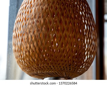 Wicker straw lampshade closeup. Natural crossed straw woven lattice texture with backlighting. Shaped lattice lamp. Light beige grid pattern. Geometric shapes and lines abstract backdrop. 3D shapes