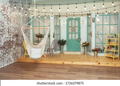 Wicker swing-hammock on the background of the summer porch of the house. Swing and summer terrace with light bulbs retro garlands. Beautiful porch with spring decorations in a photo studio