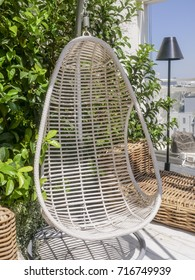 Wicker swinging sun chair suspended on a pole on an outdoor patio of an apartment against a leafy green potted plant