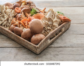 Wicker tray with variety of raw mushrooms on wooden table