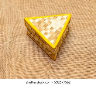 Wicker triangular box on a beige napkin.